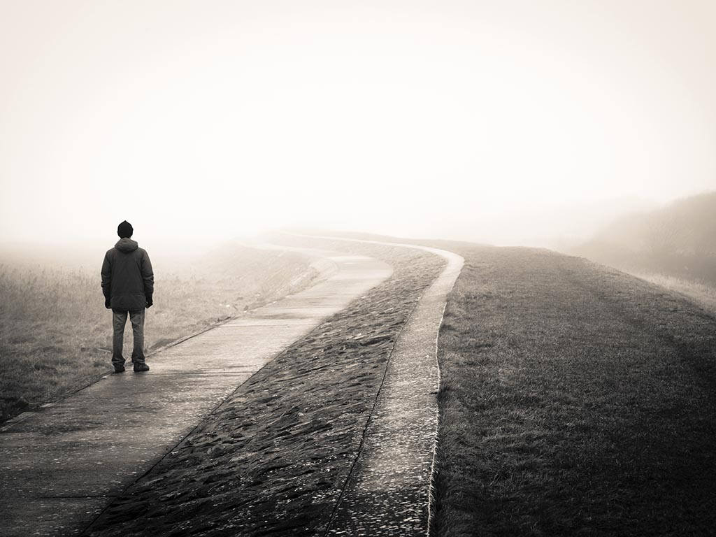 Grey Image Of a Man Standing Alone On A Road